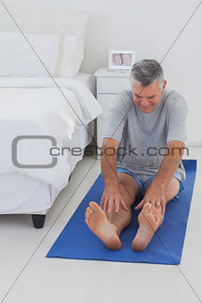 Mature man working out on mat