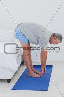 Mature man stretching on an aerobic mat