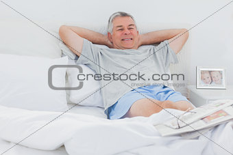 Retired man relaxing in bed