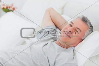 Smiling man relaxing in bed