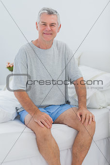 Cheerful man sitting in bed