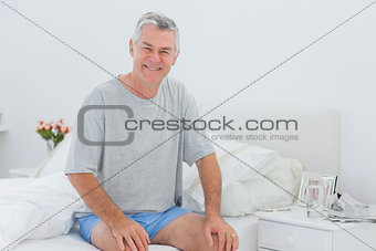 Man smiling while he is sitting on bed