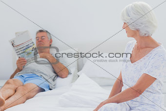 Woman looking at husband in the bed