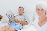 Mature man reading a newspaper in bed