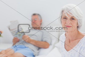 Smiling mature woman sitting in bed
