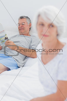 Happy woman reading a newspaper on bed