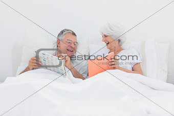 Cheerful woman showing her book to husband
