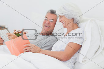 Woman showing her book to her husband