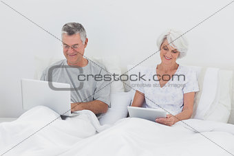 Mature man using a laptop in bed
