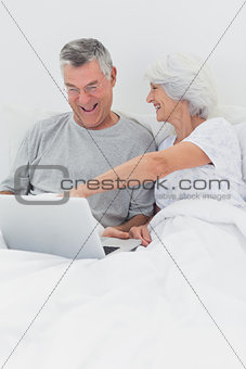 Mature woman pointing at husbands laptop