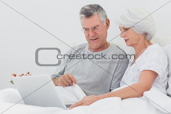 Man with wife pointing at a laptop