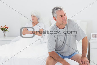 Angry man sitting in bed during a dispute
