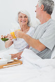Mature couple clinking their orange juice glasses