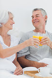 Couple clinking their orange juice glasses