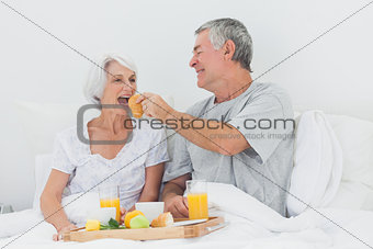 Man giving wife a croissant to wife