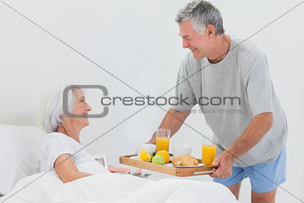 Mature man bringing wife breakfast in bed