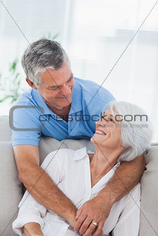 Man hugging wife who is sitting on the couch