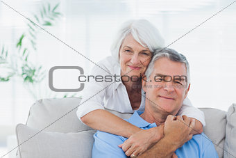 Woman embracing husband who is sitting on the couch