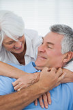 White haired woman hugging husband
