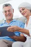 Couple using a digital tablet sitting on the couch