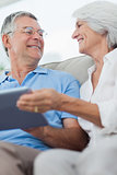 Cheerful mature couple using a digital tablet