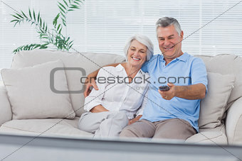 Couple watching television sitting on the couch