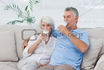 Couple drinking glasses of milk sitting on the couch