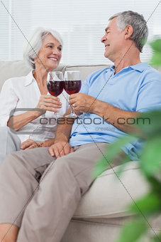 Wife and husband clinking their glasses of red wine
