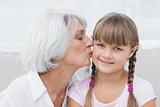 Grandmother kissing her cute granddaughter