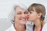 Cute little girl kissing her grandmother