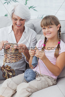 Portrait of a little girl and her granddaughter knitting together