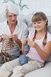 Little girl and her granddaughter knitting together