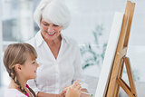 Grandmother and cute granddaughter painting together