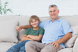 Young boy sitting on the couch with grandfather