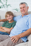 Portrait of grandson and grandfather sitting on the couch