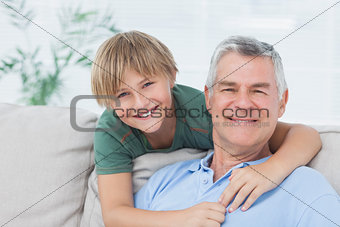 Portrait of grandson embracing grandfather