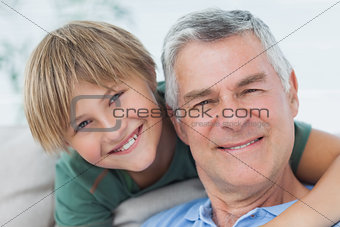 Portrait of grandson hugging grandfather