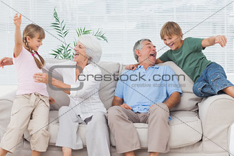 Grandchildren jumping on couch with their grandparents
