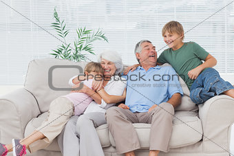 Smiling grandchildren embracing their grandparent