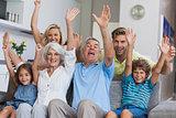Multi-generation family raising their arms
