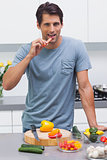 Attractive man eating a slice of bell pepper