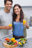 Delighted couple holding glass of orange juice
