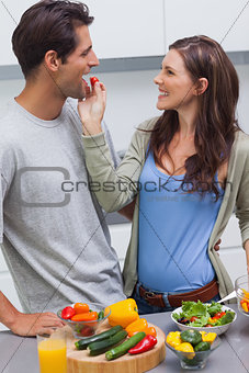 Attractive woman feeding her husband cherry tomato