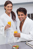 Lovely couple wearing bathrobes and holding glass of orange juice
