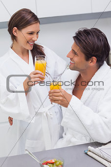 Couple clinking their glass of orange juice