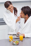 Woman wearing bathrobe feeding her husband strawberry