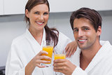 Couple holding glass of orange juice