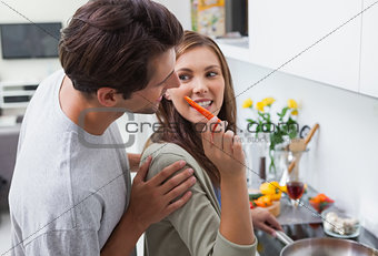 Attractive woman feeding her husband bell pepper