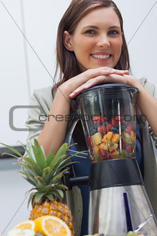 Attractive woman leaning on her blender