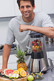 Attractive man leaning on his blender